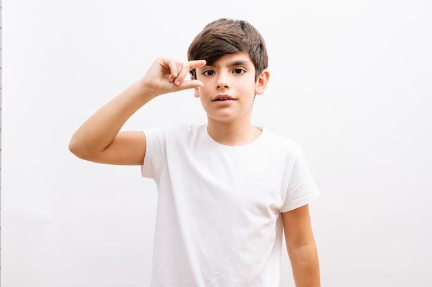 白い孤立した背景の上に立っている白いtシャツを着た若い男の子の子供は、驚いた顔、指を通して見ている目でショックを受けたokジェスチャーをしています。信じられない表情。