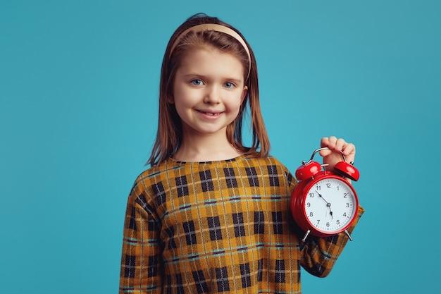 Молодая милая девушка улыбается и демонстрирует будильник на синем фоне