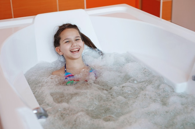 Young little cute teenager girl is sitting in the therapeutic whirlpool bath and smiles
