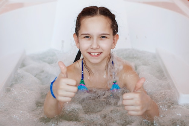 Young little cute teenager girl is sitting in the therapeutic whirlpool bathtub and give the thumbs-up to the camera.