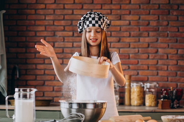 Молодая маленькая девочка, выпечки теста на кухне на завтрак