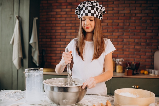 Young little girl baking pastry at the kitchen for breakfast