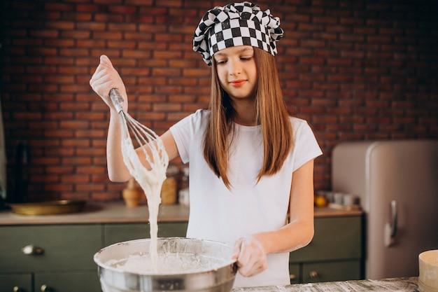 Pasticceria di cottura della bambina giovane alla cucina per la prima colazione