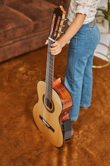 Young little girl playing guitar at home