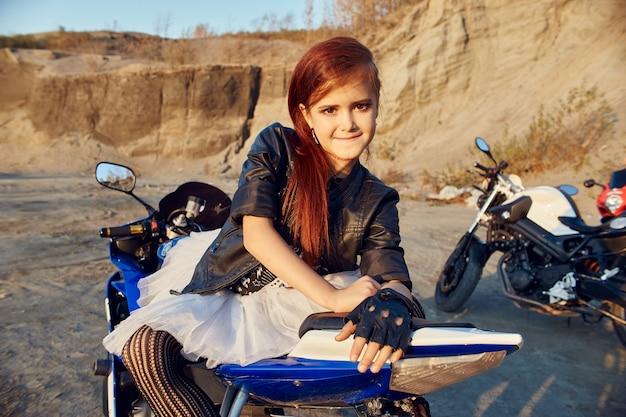 Молодая маленькая девочка, сидящая на мотоциклетных гонках, красивый маленький байкер на спортивном велосипеде на природе. дочь мотогонщика. россия, свердловск, 24 сентября 2018 г.