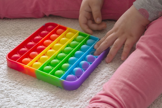 家で敷物の上に座って、新しい流行のおもちゃで遊んでいる若い女の子はそれをポップします