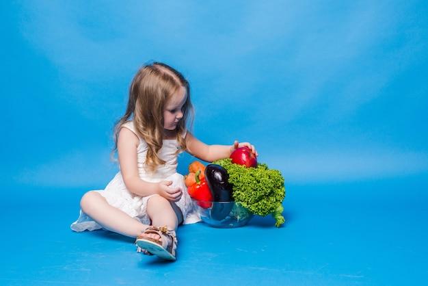 青い壁に野菜と若い女の子
