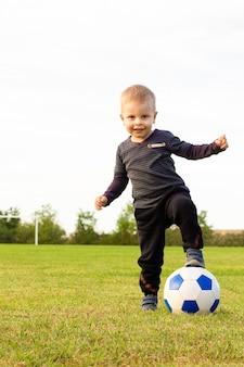 Молодой маленький ребенок 3 лет наслаждается счастливой игрой в футбол на траве городского парка, позирует, улыбаясь, гордое положение, держа мяч в детстве, спортивная страсть и здоровый образ жизни