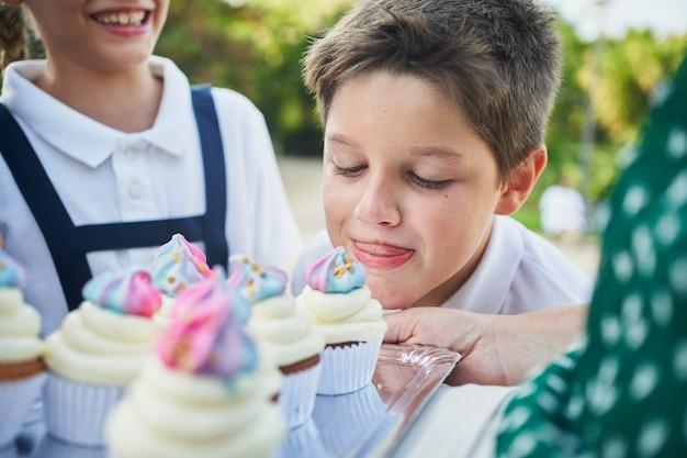 公園でカップケーキの匂いを嗅ぐ少年