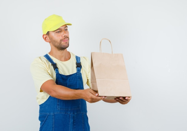 Young loader delivering paper bag and smiling in uniform front view.