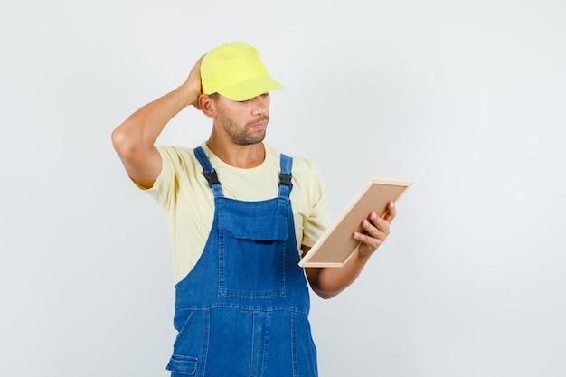 젊은 로더 유니폼에 머리에 손으로 보드를 들고 잠겨있는, 전면보기를 찾고.
