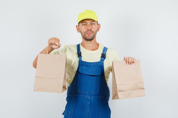 Giovane caricatore che tiene i sacchetti di carta marrone nella vista frontale uniforme.