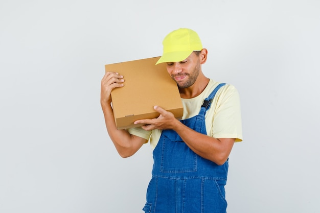 골 판지 상자를 들고 균일 한 전면보기에 웃 고 젊은 로더.