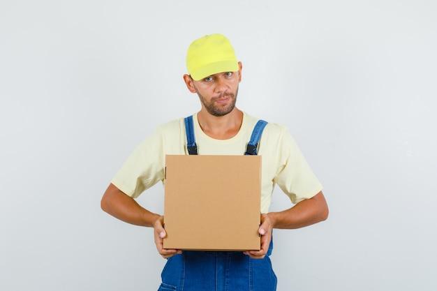 균일 한 전면보기에서 골 판지 상자를 들고 젊은 로더.