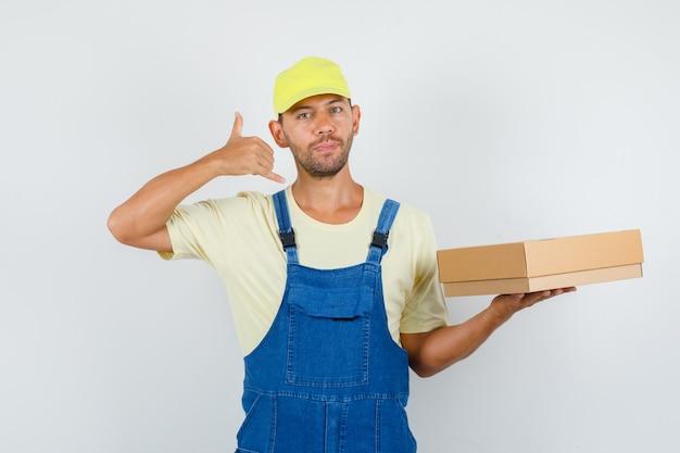Giovane caricatore che tiene la scatola di cartone con il gesto del telefono in uniforme, vista frontale.