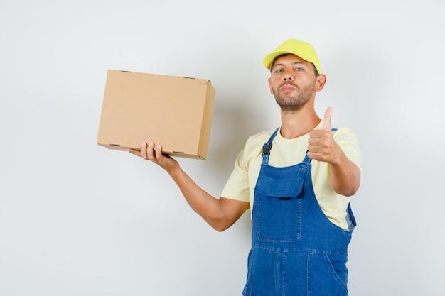 젊은 로더 유니폼에 엄지 골 판지 상자를 들고 자신감, 전면보기를 찾고.