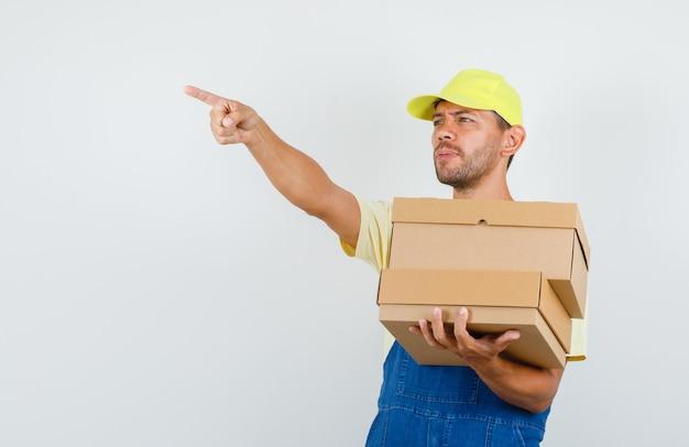 Giovane caricatore che tiene le scatole di cartone e punta lontano in uniforme, vista frontale.