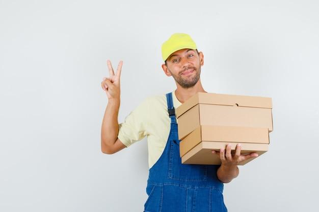 Giovane caricatore che tiene scatole di cartone con v-sign in uniforme e sembra allegro, vista frontale.