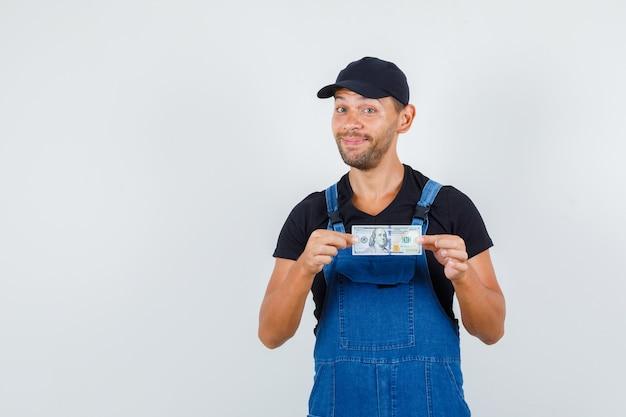 균일 하 고 쾌활 한 찾고 달러 지폐를 들고 젊은 로더. 전면보기.
