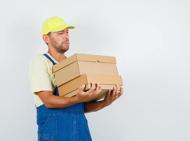 균일 한 전면보기에 무거운 골 판지 상자를 들고 젊은 로더.