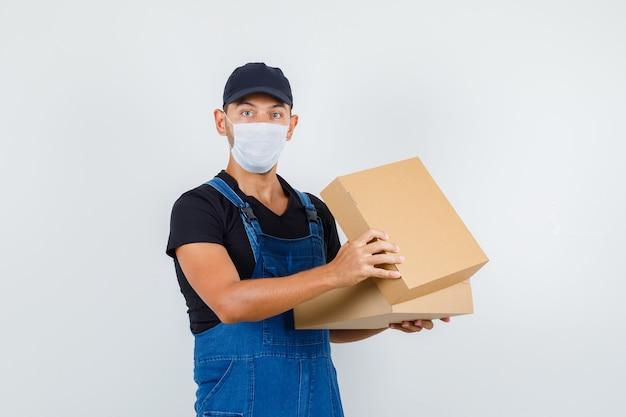 Giovane caricatore che tiene la scatola di cartone aperta in uniforme, vista frontale della maschera.