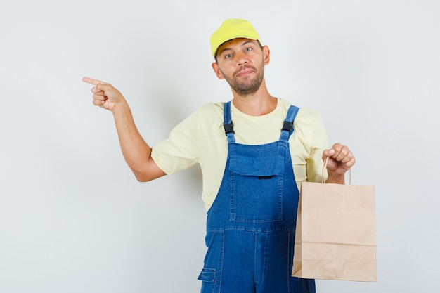 Giovane caricatore che tiene il sacchetto di carta e che punta al lato in vista frontale uniforme.