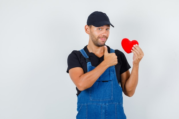Young loader holding red heart with thumb up in uniform and looking cheerful. front view.