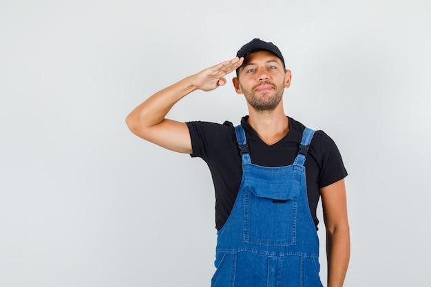 Молодой грузчик в униформе, отдавая салют и улыбаясь, вид спереди. Бесплатные Фотографии