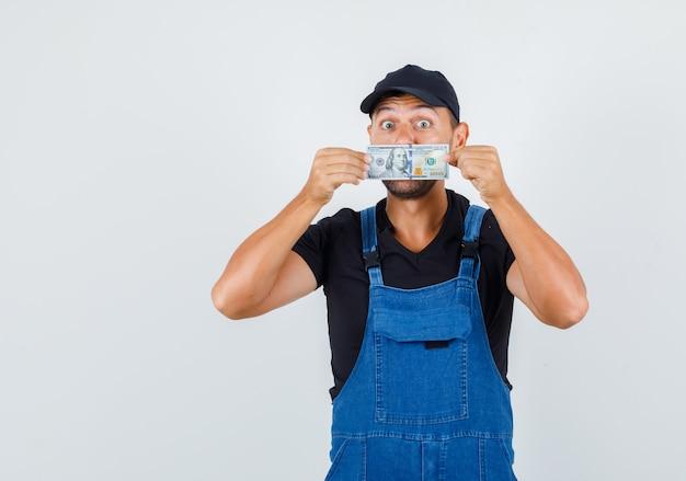 Молодой грузчик в униформе прячет рот за деньгами и осторожно смотрит, вид спереди.