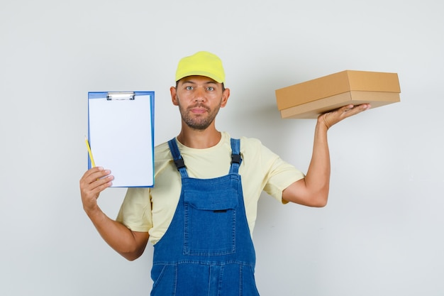 Молодой погрузчик в униформе, держа картонную коробку и буфер обмена, вид спереди.