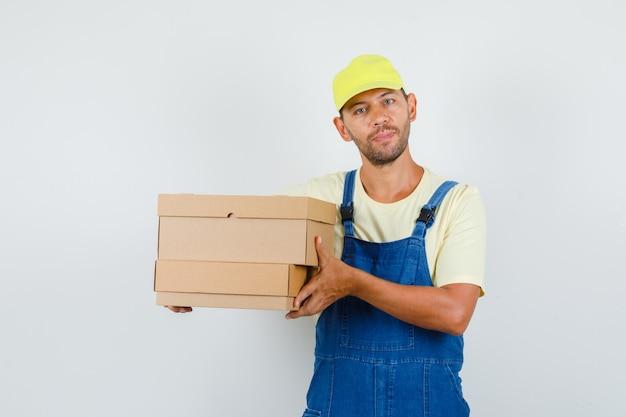 Молодой грузчик в униформе, держа картонные коробки, вид спереди.