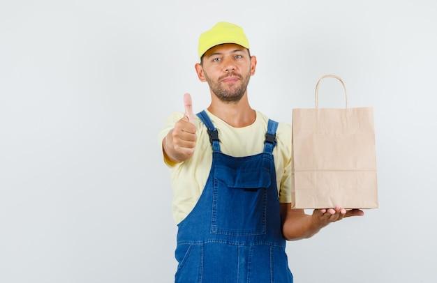 Молодой грузчик в униформе держит бумажный пакет с большим пальцем вверх и выглядит веселым, вид спереди.