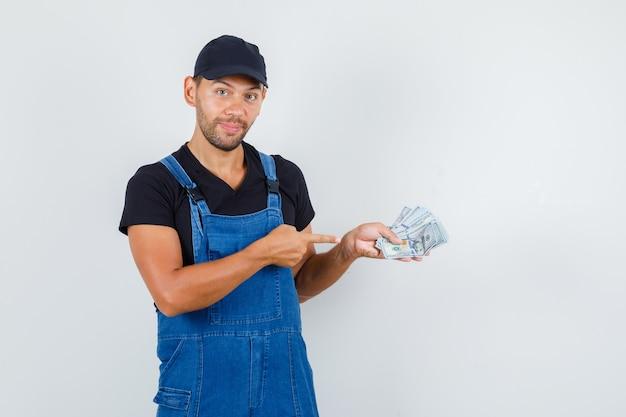 Молодой погрузчик в униформе, указывая на долларовые купюры и глядя веселый, вид спереди.