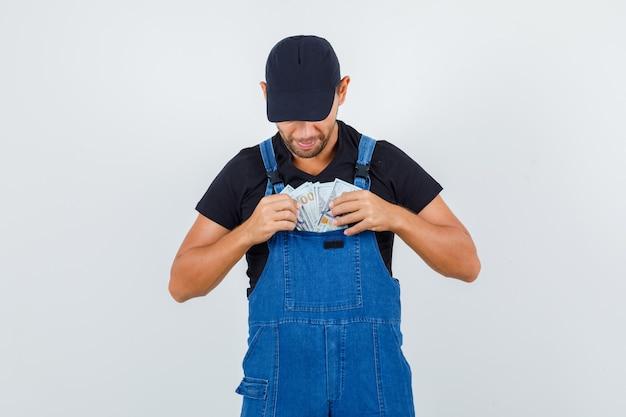 Молодой грузчик в форме вынимает деньги из кармана и смотрит внимательно, вид спереди.