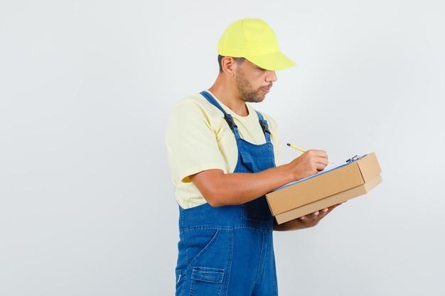 クリップボードにメモを取り、忙しい、正面図を見て制服を着た若いローダー。