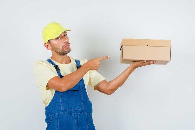 Giovane caricatore che punta alla scatola di cartone in uniforme, vista frontale.