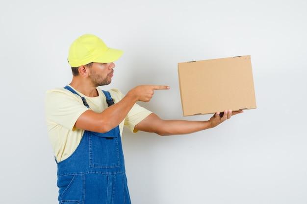 Giovane caricatore che punta alla scatola di cartone in uniforme e che sembra concentrato. vista frontale.