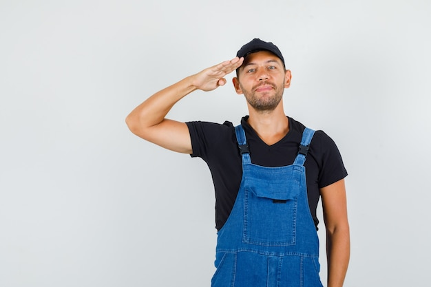 Young loader in uniform giving salute and smiling , front view.