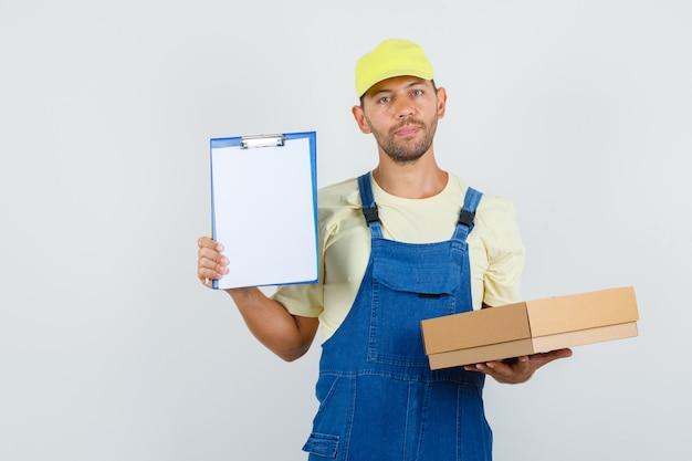 Giovane caricatore in uniforme che tiene scatola di cartone e appunti, vista frontale.