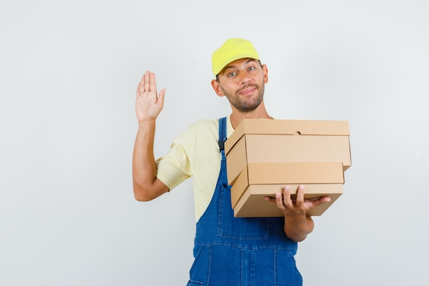 Young loader in uniform holding cardboard boxes and saying hello, front view.