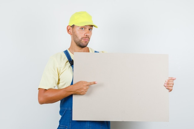 Young loader in uniform pointing at blank canvas , front view.