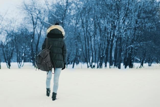 冬の雪に覆われた森を歩くバックパックを持つ若い孤独な女性