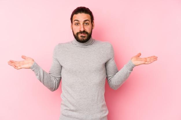 Молодой человек с длинными волосами, изолированные на розовом фоне, смущает и сомнительно пожимает плечами, чтобы удержать копию пространства.