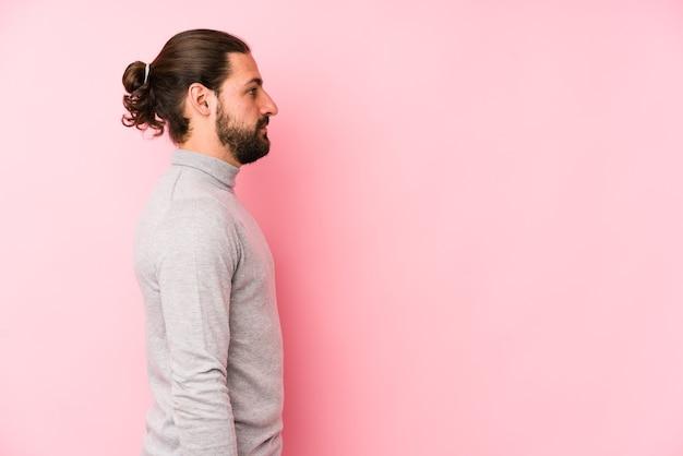 ピンクの壁に孤立した若い長い髪の男が左を見つめ、横向きのポーズ。