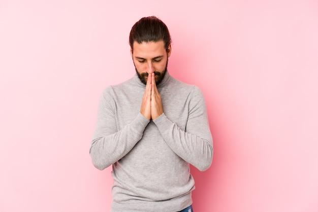 口の近くの祈りで手を繋いでいるピンクの壁に分離された若い長い髪の男は自信を持っています。