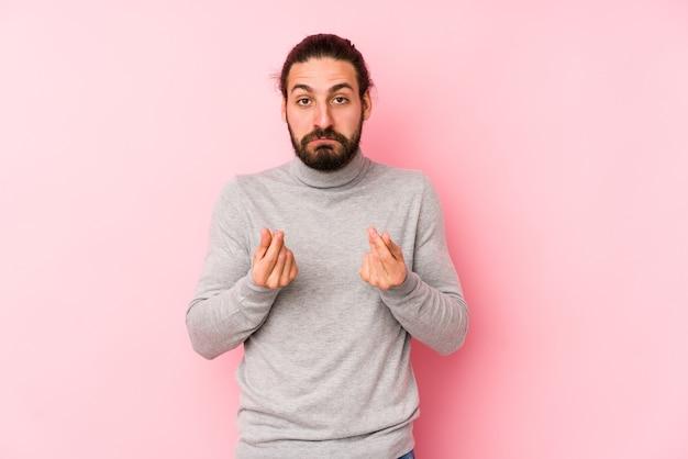Молодой человек с длинными волосами изолирован на розовой стене, показывая, что у него нет денег.