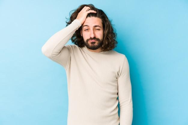若い長い髪の男が頭に手を疲れて非常に眠い青を維持する上で分離。