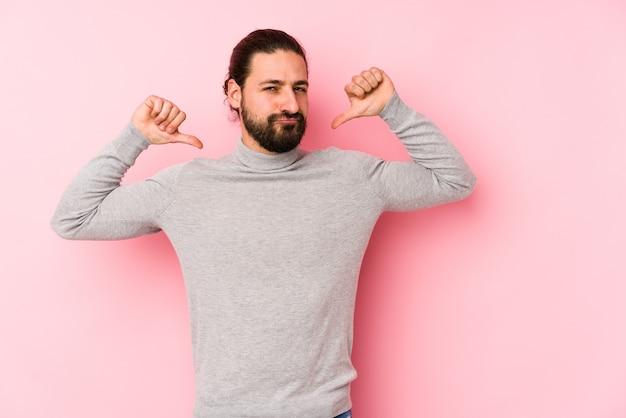 Молодой человек с длинными волосами, изолированный на розовом, чувствует себя гордым и уверенным в себе, примером для подражания.