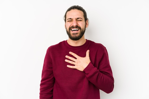 Young long hair man isolated on a white background laughs out loudly keeping hand on chest.