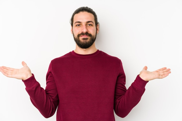 Young long hair man isolated on a white background makes scale with arms, feels happy and confident.